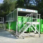 Containerstellplatz Abroller mit verfahrbarem Gerüst davor zur Ladungskontrolle