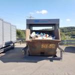 geöffnete Containerüberdachung in dem eine Mulde mit Restmüll steht