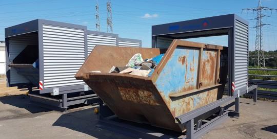 Geöffnete Containerüberdachung in dem eine Mulde mit Restmüll gelagert wird